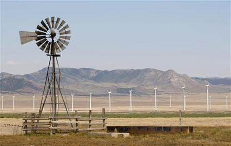 An old style windmill is pictured with newer and larger wind turbines in the background, at a wind farm near Milford, Utah May 21, 2012. REUTERS/George Frey
