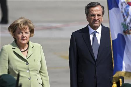 Germany's Chancellor Angela Merkel is welcomed by Greece's Prime Minister Antonis Samaras (R) upon arrival at Eleftherios Venizelos airport near Athens October 9, 2012. REUTERS/Dimitris Doudoumis//ICON