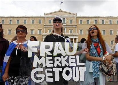 People hold a banner saying ''Frau Merkel get out'' ahead of a demonstration against the visit of German Chancellor Angela Merkel in central Athens, October 9, 2012. Merkel flew to the heart of Europe's debt crisis on Tuesday, braving protests by angry Greeks to take a message of support - but no new money - to a near-bankrupt nation fighting to stay in the Euro. REUTERS/Yannis Behrakis