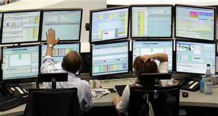 Traders work at their desks at Frankfurt's stock exchange August 8, 2011. REUTERS/Pawel Kopczynski