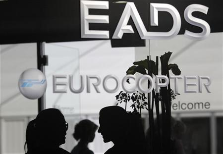 Visitors talk near the welcome desk of the EADS booth at the ILA Berlin Air Show in Selchow near Schoenefeld south of Berlin on September 13, 2012. REUTERS/Tobias Schwarz
