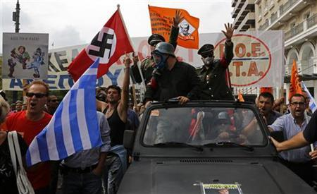 Demonstrators, dressed as Nazis, wave a Greek and a swastika flag as they ride in an open-top car in Syntagma Square in Athens as they protest against the visit of Germany's Chancellor Angela Merkel, October 9, 2012. REUTERS/Yannis Behrakis