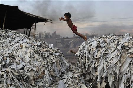A child jumps on the waste products that are used to make poultry feed as she plays in a tannery at Hazaribagh in Dhaka October 9, 2012. REUTERS/Andrew Biraj