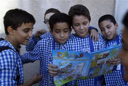 Children read an edition of the ''Qaws Quzah'' (Rainbow) magazine, in Tunis October 9, 2012. The publishers of Qaws Quzah are to be prosecuted for telling its young readers how to make a petrol bomb, officials said on Tuesday. The magazine, read for decades in Tunisia by boys and girls aged 5 to 15, has no political orientation. But the article touched a raw nerve in a country still seeking to tame the unrest stirred up by last year's successful revolution, the first of the Arab Spring. REUTERS/Zoubeir Souissi