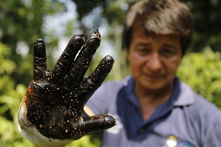 Environmentalist Donald Moncayo shows his glove after conducting a test made on an affected field in Lago Agrio, Ecuador in this January 25, 2011 file photograph. Chevron Corp on October 9, 2012 lost a U.S. Supreme Court bid to block an $18.2 billion judgment against it in Ecuador in a case over pollution in the Amazon jungle. The Supreme Court did not give any explanation for its decision, which rejected Chevron's appeal of a lower court ruling. The lower court in January had thrown out an injunction blocking enforcement of the Ecuadorean judgment. REUTERS/Guillermo Granja/Files