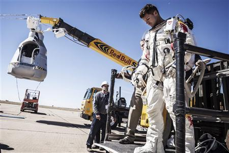 Pilot Felix Baumgartner of Austria leaves his capsule after his mission was aborted due to high winds in Roswell, New Mexico, in this October 9, 2012 handout photo. The Austrian daredevil called off his death-defying skydive from a balloon 23 miles (37 km) over the New Mexico desert on Tuesday because of winds at the launch site. REUETRS/Balazs Gardi/Red Bull Content Pool/Handout