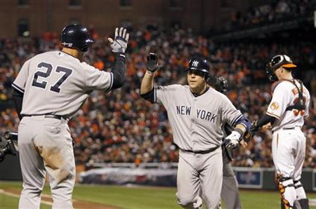 New York Yankees' Russell Martin (C) is congratulated by his teammate Raul Ibanez (L) after Martin hit a solo home run in the ninth inning against the Baltimore Orioles during Game 1 in their MLB ALDS playoff baseball series in Baltimore, Maryland October 7, 2012. REUTERS/Tim Shaffer