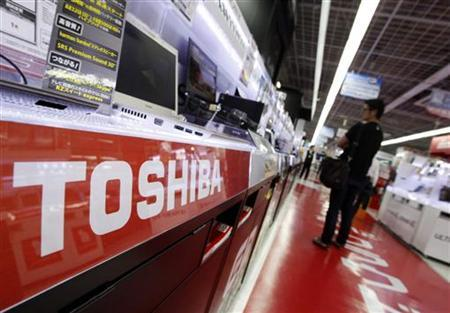 A logo of Toshiba Corp is pictured as a man looks at laptop computers at an electronics shop in Tokyo July 31, 2012. REUTERS/Yuriko Nakao