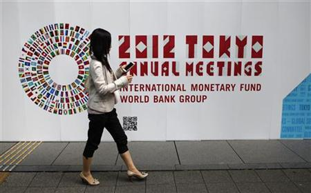 A woman walks past a signboard of the Annual Meetings of the International Monetary Fund and the World Bank Group at the Tokyo International Forum in Tokyo October 9, 2012. REUTERS/Toru Hanai