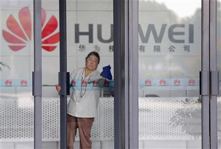 A cleaner wipes the glass door of a Huawei office in Wuhan, Hubei province October 9, 2012. REUTERS/Stringer