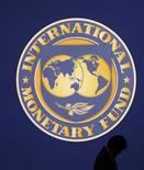 Мужчина проходит мимо логотипа МВФ в Токио 10 октября 2012 года. Международный валютный фонд призвал европейских регуляторов укрепить финансовые и бюджетные связи внутри еврозоны, поскольку необходимо срочно восстановить доверие в мировой финансовой системе. REUTERS/Kim Kyung-Hoon