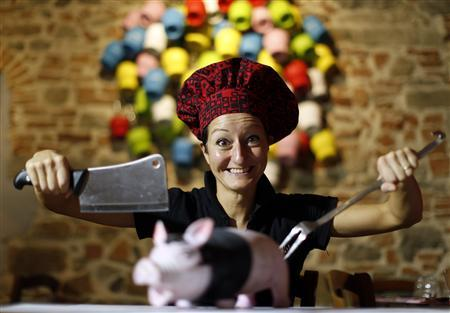 Italian chef Cristina Palanti poses with a meat cleaver and cooking fork hovering over a plastic pig figurine at the ''L'e'Maiala'' restaurant in Florence October 6, 2012. REUTERS/Alessandro Bianchi