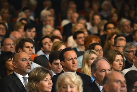 Prime Minister, David Cameron (C), listens as Chancellor of the Exchequer, George Osborne, delivers his keynote speech at the Conservative Party's annual conference, in Birmingham, central England October 8, 2012. REUTERS/Toby Melville