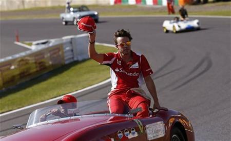 Ferrari Formula One driver Fernando Alonso of Spain waves during the driver's parade of the Japanese F1 Grand Prix at the Suzuka circuit October 7, 2012. REUTERS/Toru Hanai