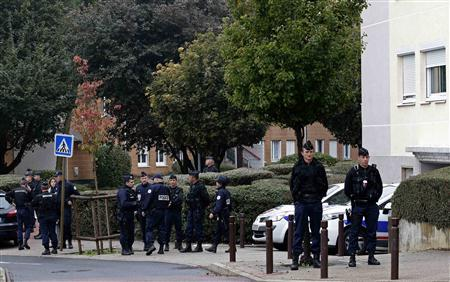 French gendarmes and police officers secure a street near a garage entrance, where an anti-terrorist raid was conducted four days ago, in Torcy near Paris October 10, 2012. REUTERS/Christian Hartmann