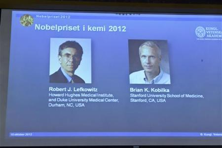 Images of researchers Robert Lefkowitz and Brian Kobilka (R) of the U.S., who won the 2012 Nobel Prize in Chemistry, are seen on a projector during a news conference by the Royal Swedish Academy of Sciences in Stockholm, October 10, 2012. REUTERS/Bertil Enevag Ericson/Scanpix