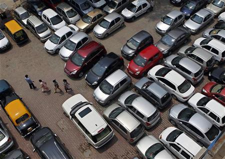 People walk through a car parking lot in New Delhi July 8, 2010. REUTERS/Adnan Abidi/Files