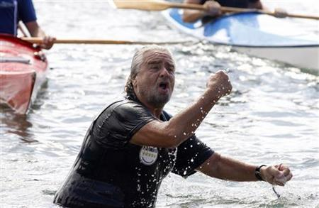 Five-Star Movement activist and comedian Beppe Grillo celebrates after swimming across the Strait of Messina from Cannitello in Calabria to Messina in Sicily as he begins his election campaign October 10, 2012. Italian elections are expected to take place in spring 2013. REUTERS/Antonio Parrinello