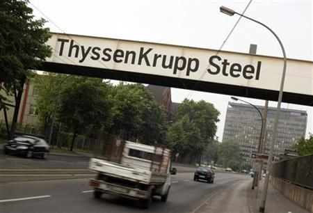 Cars drive under a banner of German industrial conglomerate ThyssenKrupp AG outside the company's steelworks in the western German city of Duisburg May 31, 2012. REUTERS/Wolfgang Rattay