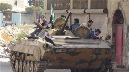 Members of the Free Syrian Army are seen around a captured Syrian Army tank after clashes, at Marat al-Numan, near the northern province of Idlib October 9, 2012. Picture taken October 9, 2012. REUTERS/Shaam News Network/Handout