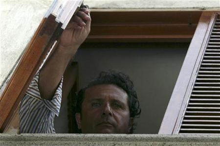 Costa Concordia cruise captain Francesco Schettino appears at a window of his apartment in Meta di Sorrento July 28, 2012. REUTERS/Gennaro Manzo