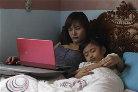Sheila Ortencio, an online contractor, takes care of her sleeping daughter as she works on her computer inside a bedroom of their house in Lipa city, south of Manila October 5, 2012. REUTERS/Romeo Ranoco