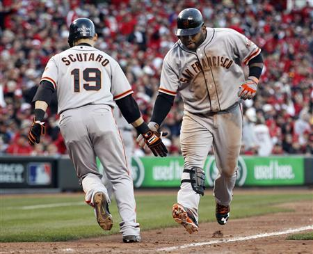 San Francisco Giants third baseman Pablo Sandoval (R) slaps hands with teammate Marco Scutaro after driving him home with a seventh inning two-run home run against the Cincinnati Reds during Game 4 of their MLB NLDS playoff baseball series in Cincinnati, Ohio October 10, 2012. REUTERS/Jeff Haynes