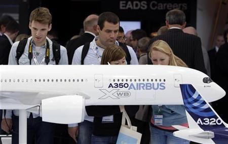 Visitors look at an A350 aircraft miniature at the EADS booth during the ILA Berlin Air Show in Selchow near Schoenefeld south of Berlin on September 13, 2012. REUTERS/Tobias Schwarz