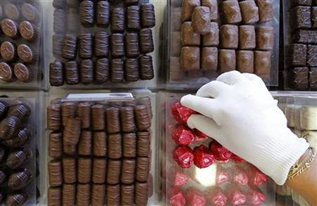 A shop assistant adjusts pralines in a counter at a Leonidas chocolate boutique in Brussels September 28, 2011. REUTERS/Yves Herman/Files