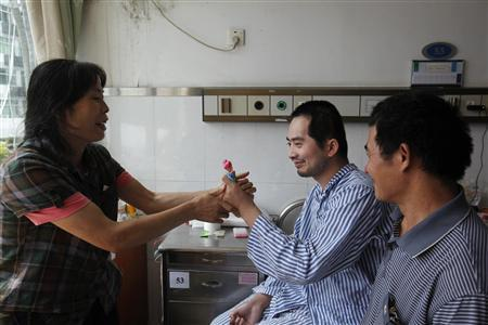 Zhang Tingzhen (C) is given a doll to play with by his mother Wei Xiuying while sitting beside his father Zhang Guangde at a Shenzhen hospital in southern China September 26, 2012. REUTERS/Stringer