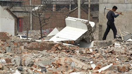 A man carries a pick over his shoulder as he walks through the rubble of demolished dwellings in a ''hutong'', or small alley, in Beijing April 8, 2010. China risks growing social instability and even violence if the government does not take effective action to address rising public anger about forced evictions and demolitions, according to a report released last week by the Chinese Urgent Action Working Group, a China-based rights lobby. REUTERS/David Gray