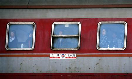 Passengers aboard a train look out of windows as it approaches a Beijing station October 10, 2012. REUTERS/David Gray