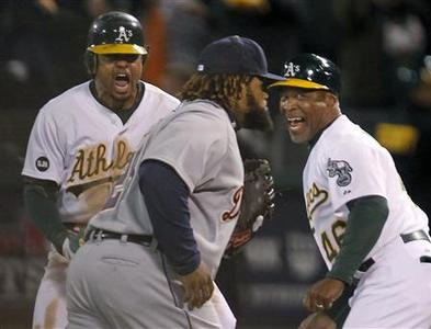Oakland Athletics center fielder Coco Crisp (L) and first base coach Tye Waller celebrate Crisp's game winning RBI in the 9th inning as Detroit Tigers first baseman Prince Fielder (28) walks off the field during Game 4 of their MLB ALDS playoff baseball series in Oakland, California October 10, 2012. REUTERS/Robert Galbraith