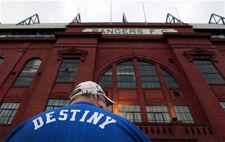 A Rangers fan stands outside Ibrox Stadium in Glasgow, Scotland February 14, 2012. REUTERS/David Moir