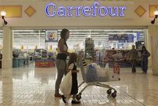 Покупатели проходят мимо магазина Carrefour на западе Дохи, 20 сентября 2012 года. Сравнимые продажи крупнейшей в Европе розничной чести Carrefour выросли на 0,2 процента в третьем квартале за счет стабильного спроса в Латинской Америке и некоторого улучшения показателей во Франции. REUTERS/Fadi Al-Assaad