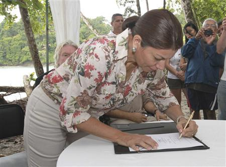 Costa Rica's President Laura Chinchilla signs an order banning shark finning in the coastal waters of Costa Rica, at Manuel Antonio National Park in Quepos, 157 km (98 miles) off San Jose, October 10, 2012. REUTERS/Roberto Montero/Costa Rica Presidency/Handout