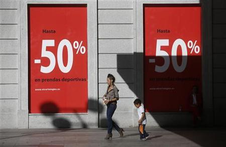 People walk past a banner advertising sales in a shopping mall in Madrid October 9, 2012. REUTERS/Juan Medina