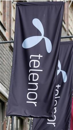 The Telenor logo hangs on flags outside one of their stores in Stockholm October 26, 2007. REUTERS/Bob Strong