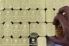 Рабочий завода PT Antam Tbk в Джакарте укладывает 100-граммовые слитки золота, 13 июля 2012 года. Цены на золото растут после четырех дней снижения несмотря на сокращение кредитного рейтинга Standard & Poor's для Испании. REUTERS/Beawiharta