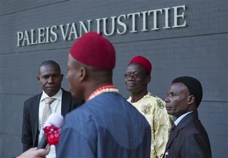 Alali Efanga (L), Eric Dooh (2nd L), Chief Fidelis Oguru (2nd R) and Friday Alfred Akpan, all representatives of farmers from Nigeria are interviewed by a Dutch television crew in front of a local court in The Hague October 11, 2012. REUTERS/Michael Kooren