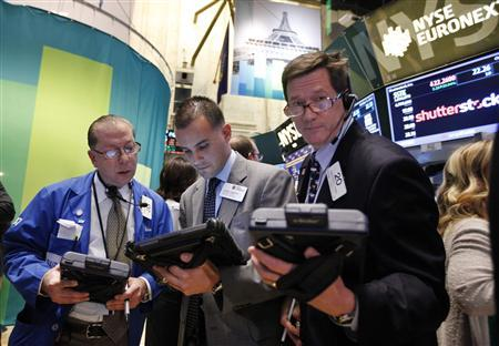 Traders work in front of a trading board showing Shutterstock Inc on the floor of the New York Stock Exchange, October 11, 2012. Shutterstock Inc soared as much as 32 percent in its market debut, a day after the online stock photography provider priced its shares above its expected range. REUTERS/Brendan McDermid