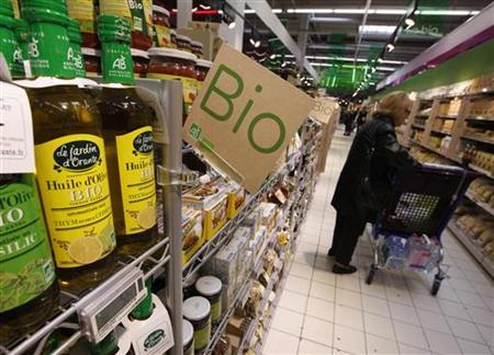 A customers buys organic products in the Bio foods section at Carrefour Planet supermarket in Nice Lingostiere November 29, 2011. REUTERS/Eric Gaillard