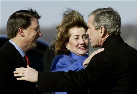 President George W. Bush (R) gets a hug from Elizabeth Dole (C) as Charlotte, North Carolina Mayor Pat McCrory looks on during the president's arrival in Charlotte, North Carolina February 27, 2002. REUTERS/Kevin Lamarque KL