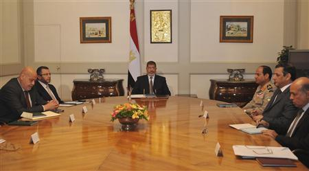 Egypt's President Mohamed Mursi (C) meets with Egypt's ministers at the Presidential Palace in Cairo October 11, 2012. Egypt's president removed the general prosecutor from his post on Thursday, appeasing demonstrators who accused him of presenting weak evidence in a case against Mubarak-era officials accused of planning attacks on protesters last year. REUTERS/Egyptian Presidency/Handout