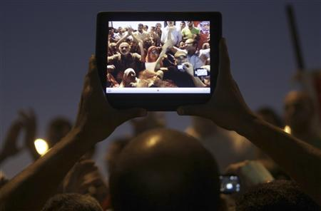 Egyptian protesters are pictured on a tablet device during a protest against general prosecutor Abdel Maguid Mahmoud and the Mubarak regime at Tahrir Square, the focal point of the Egyptian uprising, in Cairo October 11, 2012. Egypt's president removed the general prosecutor from his post on Thursday, appeasing demonstrators who accused him of presenting weak evidence in a case against Mubarak-era officials accused of planning attacks on protesters last year. REUTERS/Amr Abdallah Dalsh
