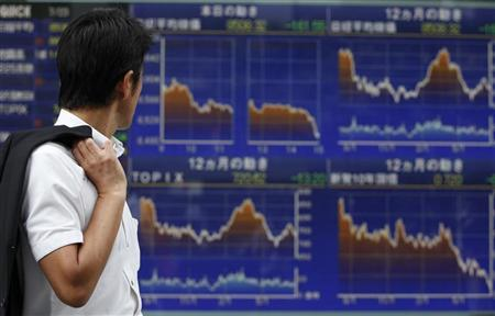 A man looks at an electronic board displaying graphs of various market indices outside a brokerage in Tokyo July 23, 2012. REUTERS/Yuriko Nakao