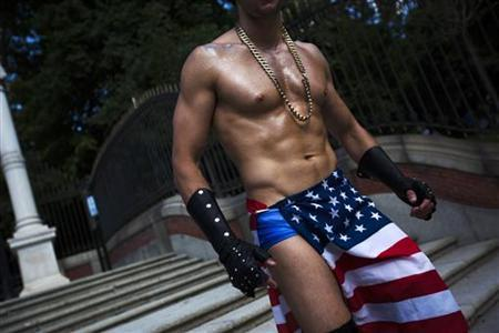 A reveller draped in a U.S. flag heads to take part in the Gay Pride parade in Madrid June 30, 2012. REUTERS/Susana Vera/Files