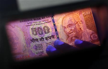 An employee uses checks an Indian currency note at a cash counter inside a bank in Mumbai June 21, 2010. REUTERS/Rupak de Chowdhuri/Files