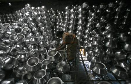 A worker checks aluminium utensils inside a factory on the outskirts of Agartala, capital of Tripura October 12, 2012. REUTERS/Jayanta Dey