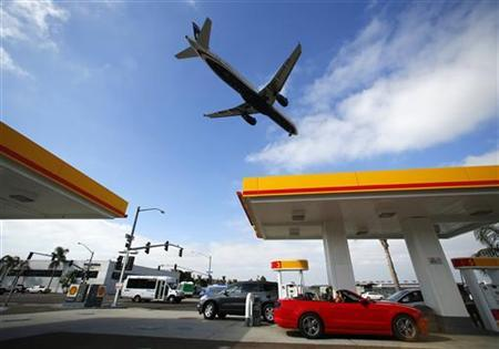 Consumers purchase gasoline at a gas station as a plane approaches to land at the airport in San Diego, California October 8, 2012. REUTERS/Mike Blake